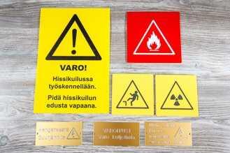 Varoituskyltit kaiverrettuna muovista.